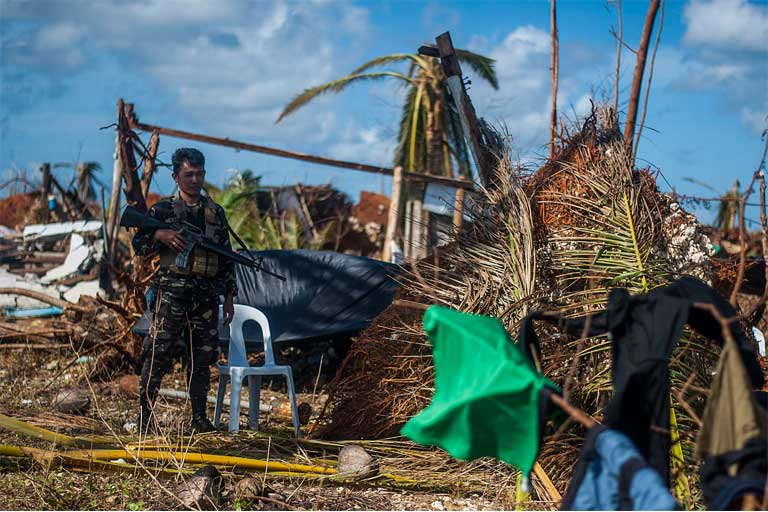 A Filipino marine stands guard at the village of Guiuan in the aftermath of Super Typhoon Haiyan. Photo by Mass Communication Specialist Seaman Liam Kennedy courtesy of the U.S. Navy.